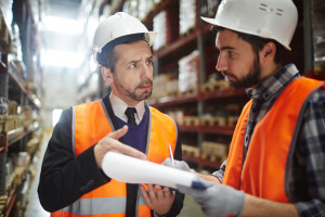 Portrait of warehouse worker talking to supervising manager whil